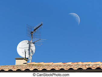 tv antenna and moon - tv antenna on a house roof under the...