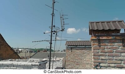 Tv antenna in town. Rooftops and sky. Media and...