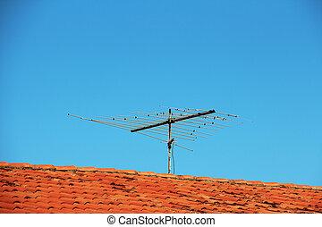 TV antenna on roof - VHF TV antenna on roof over blue sky.