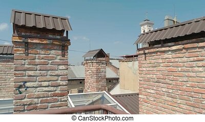 Tv antenna on the roof. Town rooftops and sky. History of...