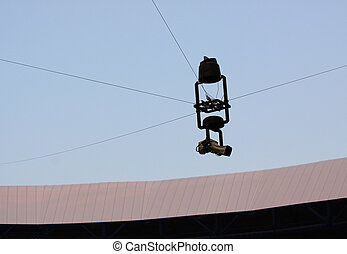 tv spider camera flying on cord above playing field