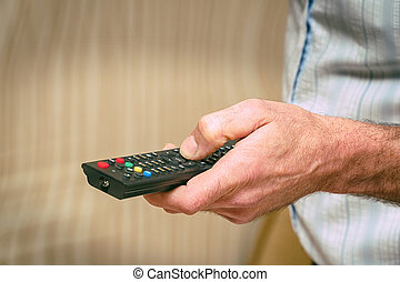 TV remote in the hand of man