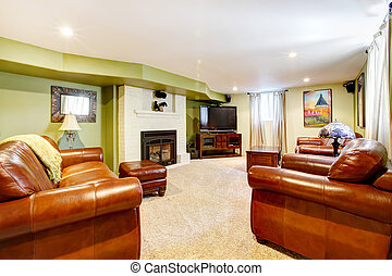 Tv room with green walls, leather sofas and fireplace.