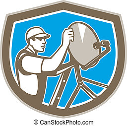 Illustration of a TV satellite dish installer set inside shield crest on isolated background done in retro style.