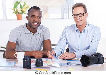 twórczy, co-workers., dwa, radosny, handlowy zaludniają, w, przypadkowy chodzą, posiedzenie razem, na stole, i, aparat fotograficzny przeglądnięcia