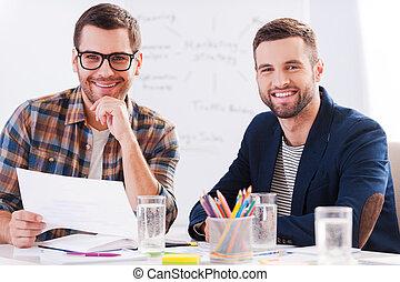 twórczy, koledzy., dwa, radosny, biznesmeni, w, przemądrzały przypadkowy, nosić, posiedzenie razem, na stole, i, aparat fotograficzny przeglądnięcia