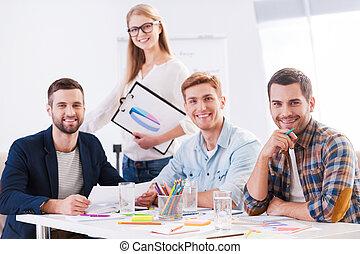 twórczy, team., cztery, radosny, handlowy zaludniają, w, przemądrzały przypadkowy, nosić, posiedzenie razem, na stole, i, aparat fotograficzny przeglądnięcia