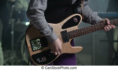 Close up of electric guitar played by unrecognizable musician at concert