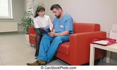 twee, artsen, een, man, en, een, vrouw, zijn, zittende , op, een, sofa, in, de, kliniek, en, sprekend aan, elke, andere., 4k