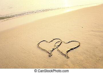 twee harten, getrokken, in, strand, in, ondergaande zon