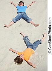 twee kinderen, het liggen, op, zand