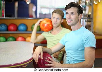 twee mannen, zetten, bij lijst, in, bowling, houden, gelul, en, blik, up;, brandpunt, op, rechts, man;, ondiep, diepte van gebied