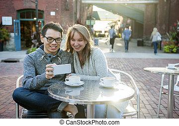 twee mensen, met, smartphone, in, koffiehuis