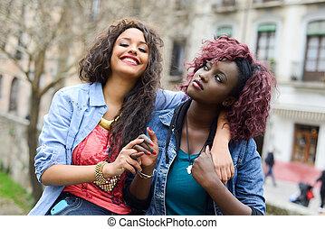 twee, mooie meisjes, in, stedelijke , backgrund, zwarte en, gemengd, vrouwen