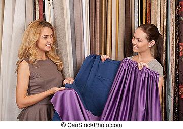 twee, mooie vrouwen, het vergelijken, textile., jonge, blonde , staand, in, winkel, en, het glimlachen