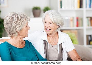 twee, seniore vrouwen, kletsende, in, de, woonkamer