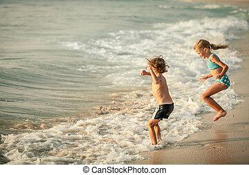 twee, vrolijke , kinderen spelende, op het strand