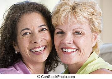 twee vrouwen, in, woonkamer, het glimlachen