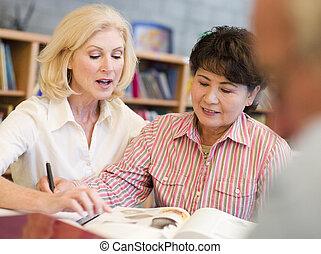 twee vrouwen, zittende , in, bibliotheek, dichtbij, een, man, met, een, boek, en, notepad, (selective, focus)