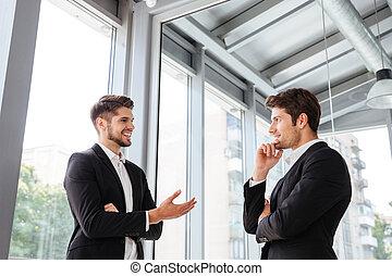 twee, zakenlieden, het glimlachen, en, klesten, in, kantoor
