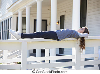 Tween kid girl relaxing on a park fence