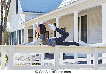 Tween kid girl training gymnastics on a fence