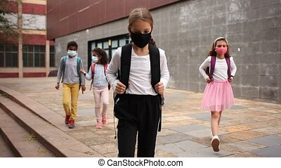 Tween schoolchildren in protective masks with backpacks going to school lessons on autumn day. Back school concept during pandemic. High quality FullHD footage