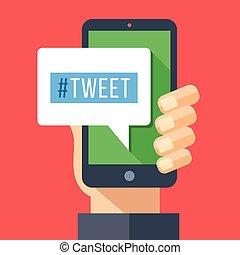 Tweet message on smartphone screen. Hand holding smartphone....