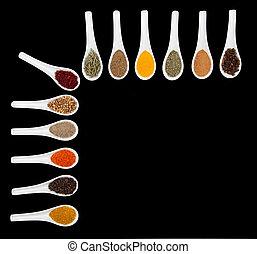 Twelve spices on black background
