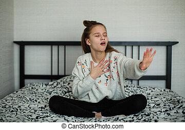 Twelve year old cute girl having fun in her room sitting on the bed.