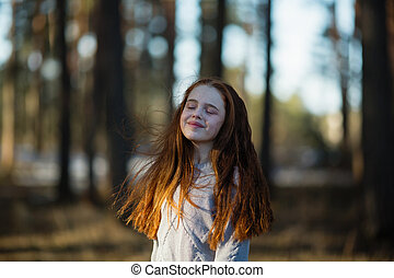 Twelve-year-old cute girl with long red hair posing for the camera in the park, photo shoot outdoors.