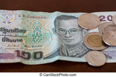 Twenty Baht note from Thailand with coins