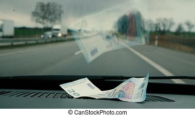 Twenty euros placed in the car to the front glass. Close up...