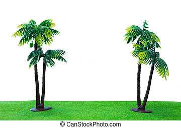 Twic toy coconut tree on grass with isolated white background