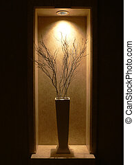 Twigs arranged in vase in illuminated alcove. Banff Springs Hotel, Banff National Park, Alberta, Canada.