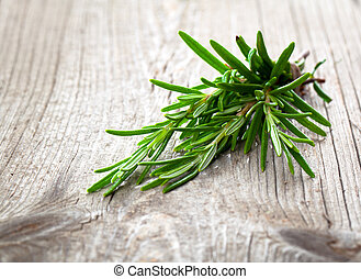 Twigs of rosemary on wooden texture