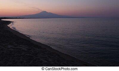 Twilight Agnone Bagni sea beach with smoky Etna volcano in...
