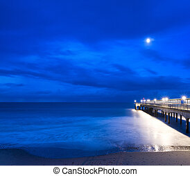 Twilight landscape of pier stretching out into sea with moonlight