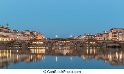 Twilight sky scene of Ponte Alla Carraia and Santa Trinita Holy Trinity Bridge day to night timelapse over River Arno