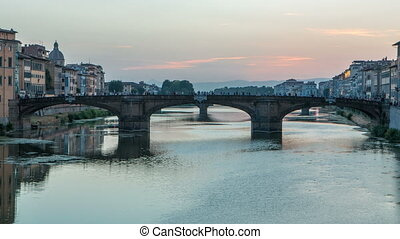 Twilight sky scene of Ponte Santa Trinita Holy Trinity Bridge day to night timelapse over River Arno
