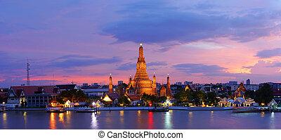 Panorama view of Twilight time Wat Arun across Chao Phraya River during sunset in Bangkok, Thailand