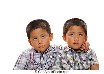 Twin asian boys cuddle and look cute