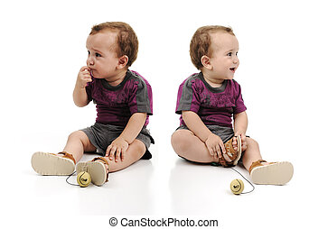 Twin baby boys are sitting together. One baby is angry sad crying and another is happy. Studio shot.