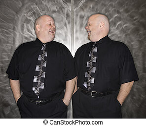 Twin bald men laughing. - Caucasian bald mid adult identical...