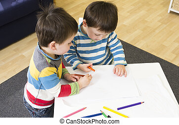 Twin boys drawing at a table together