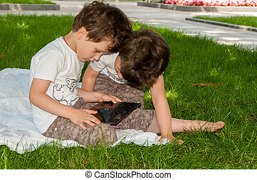 twin boys looking at the tablet on nature in the park