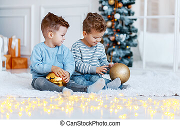 Twin brothers in front of the christmas tree with candles and gifts. love, happiness and big family concept