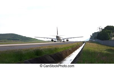 Twin-engine aircraft rolls on the runway. Day. Airfield Phuket International Airport. Slow Motion. Close-up.