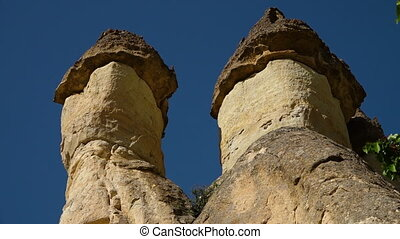 Twin erect-topped rock formation tops against a blue sky -...