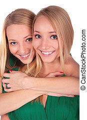 Twin girls embrace from behind